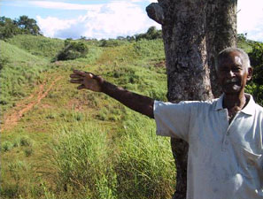 This peasant farmer's land has a 200 meter wide cleared corridor where the two oil pipelines pass through. The pipelines have disrupted water supplies so badly that he can no longer work the farm. He has lost his fish ponds and a small mine as well as his animals and his crops. His family has moved away.